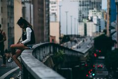 Girl sitting on ledge above a road Royalty Free Stock Image