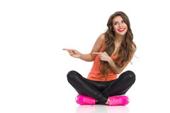 Girl Sitting With Legs Crossed And Pointing. Smiling young woman in orange shirt, black leather trousers and pink sneakers sitting on a floor with legs crossed Stock Image