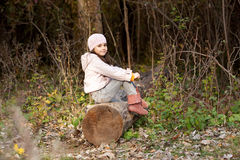 Girl sitting on a log in the woods Stock Images