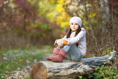 Girl sitting on a log in the woods Stock Photos