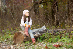 Girl sitting on a log in the woods Royalty Free Stock Photos