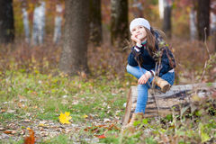 Girl sitting on a log in the woods Royalty Free Stock Photography