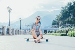 Girl sitting on longboard outdoor. Royalty Free Stock Photo