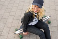 Girl sitting on longboard. And smiling Stock Photos
