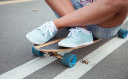 Girl sitting on a longboard Stock Photos