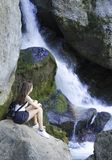 Girl sitting and looking on falling water stock photo