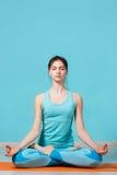 Girl sitting in lotus pose. On rug Royalty Free Stock Photos