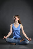 Girl sitting in the lotus position Stock Image