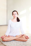 The girl sitting in the Lotus position Royalty Free Stock Photography