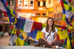 Girl sitting in the Lotus position on Buddhist stupa, prayer flags flying Stock Photos