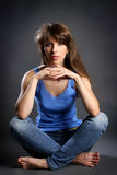 Girl sitting in the lotus position in jeans on a gray Stock Images