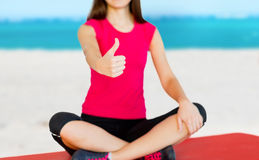 Girl sitting in lotus position with thumbs up Royalty Free Stock Photography