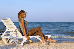 Girl sitting on a lounge chair Stock Photography