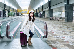 Girl sitting on luggage in the airport hall Royalty Free Stock Photo
