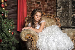 Girl sitting in a luxury chair next to the Christmas tree Royalty Free Stock Images
