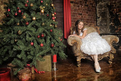 Girl sitting in a luxury chair next to the Christmas tree Stock Photography