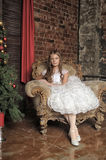 Girl sitting in a luxury chair next to the Christmas tree Royalty Free Stock Photos