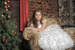 Girl sitting in a luxury chair next to the Christmas tree Stock Photo