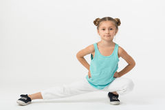 A girl sitting  and makes gymnastic exercise Stock Images