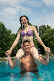 Girl sitting on man's shoulders at swimming pool Royalty Free Stock Image