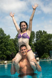 Girl sitting on man's shoulders at swimming pool Stock Photo