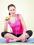 Girl sitting on a mat and holding an apple Royalty Free Stock Photo