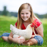 Girl sitting on a meadow with her chicken Royalty Free Stock Photo