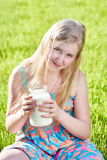 Girl sitting in meadow with a jug of milk Stock Image