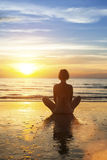 Girl sitting meditation on the ocean during an amazing sunset. Stock Image