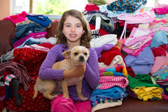 Girl sitting on a messy clothes sofa with chihuahua dog Stock Photo