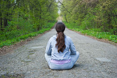 Girl sitting in the middle of a forest road Stock Photo