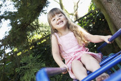 Girl Sitting on monkey bars in backyard portrait Stock Image