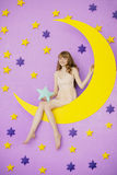Girl sitting on the moon toy Stock Photography