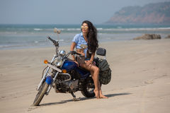 The girl is sitting on a motorcycle. A girl is sitting on a motorcycle on the beach Stock Images