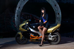 Girl sitting on a motorcycle at night. Biker girl sitting on a motorcycle at night. beautiful black-haired woman in a short skirt sitting on a sports bike Stock Photography