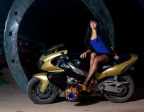 Girl sitting on a motorcycle at night. Biker girl sitting on a motorcycle at night. beautiful black-haired woman in a short skirt sitting on a sports bike Royalty Free Stock Images