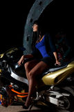 Girl sitting on a motorcycle at night. Biker girl sitting on a motorcycle at night. beautiful black-haired woman in a short skirt sitting on a sports bike Stock Images