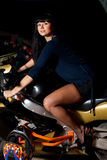 Girl sitting on a motorcycle at night. Biker girl sitting on a motorcycle at night. beautiful black-haired woman in a short skirt sitting on a sports bike Royalty Free Stock Photo