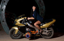 Girl sitting on a motorcycle at night. Biker girl sitting on a motorcycle at night. beautiful black-haired woman in a short skirt sitting on a sports bike Royalty Free Stock Image