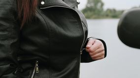 A girl sitting on a motorcycle puts on her leather jacket. Biker fastens leather jacket. 4k slow motion