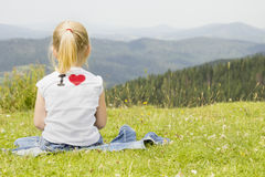girl sitting on a mountain top Royalty Free Stock Images