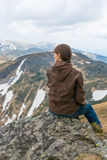 Girl is sitting on a mountain top Stock Photo