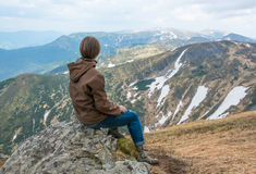 Girl is sitting on a mountain top Stock Photography