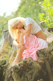 Girl sitting on a nature with hand on knees Stock Image