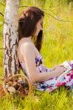 Girl sitting near basket of mushrooms , reading stock image