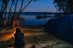 Girl is sitting near bonfire. Blue Camping Tent Illuminated Inside. Night Hours Campsite. Recreation and Outdoor. Lake. hiking, stock photo