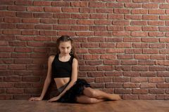 Girl sitting near brick wall. Girl in black skirt sitting near brick wall in studio royalty free stock image