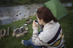 Girl sitting near a campfire at the campsite looking at map and drinking coffee. Royalty Free Stock Photo