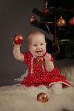 Girl  sitting near Christmas tree. Little girl in red dress sitting near Christmas tree, indoor Royalty Free Stock Photos