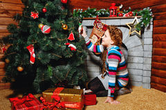 Girl sitting near Christmas tree Royalty Free Stock Photo
